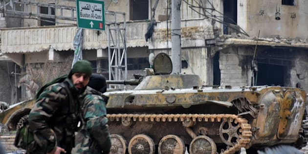 TOPSHOT - Syrian pro-government forces patrol the northern embattled city of Aleppo on December 14, 2016.  Shelling and air strikes sent terrified residents running through the streets of Aleppo as a deal to evacuate rebel districts of the city was in danger of falling apart.   / AFP / George OURFALIAN        (Photo credit should read GEORGE OURFALIAN/AFP/Getty Images)
