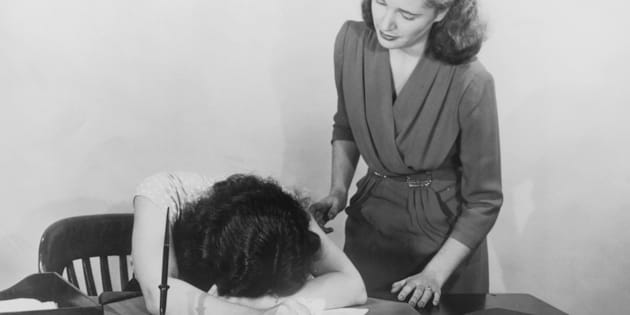 A woman moves to comfort a co-worker who is slumped over her desk in despair, circa 1940. (Photo by FPG/Hulton Archive/Getty Images)