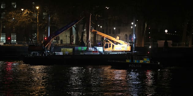 A police launch passes a barge moored on the River Thames in central London, as a suspected unexploded Second World War bomb has been found in the river, forcing the closure of Waterloo and Westminster bridges in London.