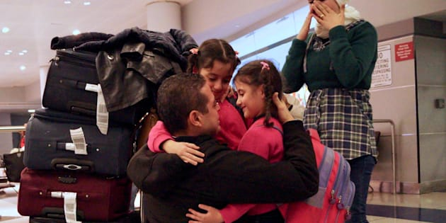 Fadi Kassar (L), hugs his daughters Hnan, 8 and Lian, 5 for the first time in more than 2 years as his wife Razan looks on after the family was reunited at John F. Kennedy International airport in New York City following a flight from Amman, Jordan, February 2, 2017. 