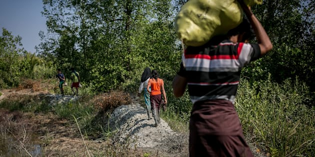 A Rohingya family fleeing from Dekibonia village in Myanmar crosses into Bangladesh on Feb. 6.