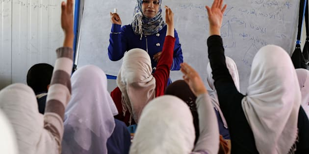 Syrian refugee children raise their hands as they attend class in a UNICEF school at the Al Zaatari refugee camp in the Jordanian city of Mafraq, near the border with Syria March 11, 2015. Nearly four million people have fled Syria since 2011, when anti-government protests turned into a violent civil war. Jordan says it is sheltering around 1.3 million refugees.  REUTERS/Muhammad Hamed (JORDAN - Tags: CIVIL UNREST CONFLICT SOCIETY IMMIGRATION EDUCATION)