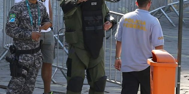 An agent of the bomb squad in protective clothing stands in the area near the finishing line of the men's cycling road race at the 2016 Rio Olympics after they made a controlled explosion, in Copacabana, Rio de Janeiro, Brazil August 6, 2016.