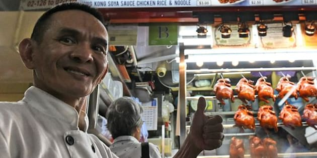 Singaporean chef Chan Hon Meng poses infront of his Hong Kong Soya Sauce Chicken Rice and Noodle stall in Singapore on July 22, 2016.