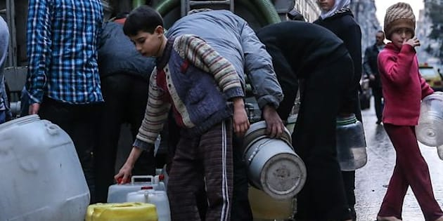 SYRIA. MARCH 5, 2016. Children fill containers with drinking water from a tanker in Salah al-Din, Aleppo. Valery Sharifulin/TASS (Photo by Valery Sharifulin\TASS via Getty Images)