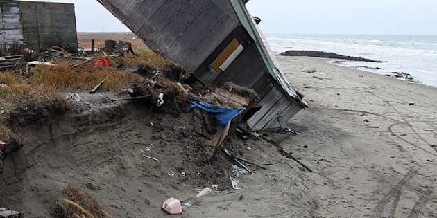 A home destroyed by beach erosion tips over inSeptember 2006 in the Alaskan village of Shishmaref.