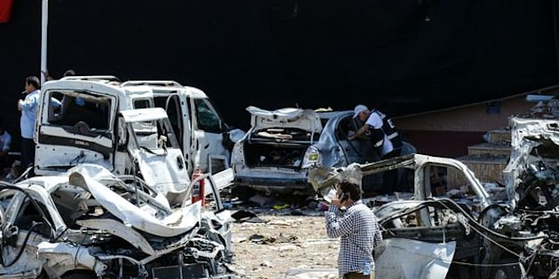 A man walks among the wreckage of vehicles as Turkish rescue workers and police inspect the blast scene following a car bomb attack in theTurkish city of Elazig.