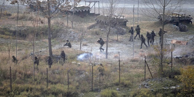 Indian army soldiers search for suspected militants as smoke rises from a bunker after a gunbattle in Mohra in Uri.