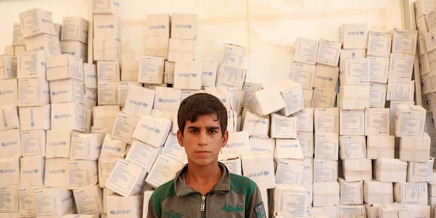Rayan stands in the tent for new arrivals at Salamiyah camp. The UNICEF boxes behind him are UNICEF's hygiene kits that form part of the Multi-Sectoral Emergency Package (MSEP) to which WFP and UNFPA also contribute.