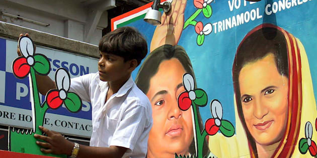 An Indian boy gives the finishing touches to the symbol of the regional Trinamool Congress party in front of a painting of party leader Mamata Banerjee (L), and leader of India's main oppostion Congress Party Sonia Gandhi ahead of an election rally in Calcutta May 2, 2001.