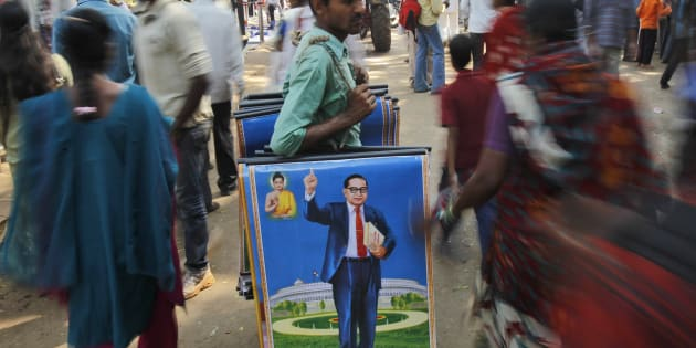 A man holds posters of B.R. Ambedkar for sale on his death anniversary in Mumbai, on 6 December 2011. (AP Photo/Rafiq Maqbool)