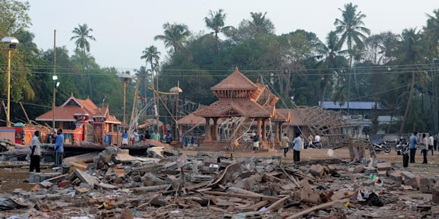 Indian bystanders gather among debris and building wreckage of The Puttingal Devi Temple in Paravur some 60kms north-west of Thiruvananthapuram on April 11, 2016.  More than 100 people have died and 350 injured when fireworks meant to be lit for festivities caught fire and exploded near the temple where thousands of people had gathered to witness the festivities on the early hours of April 10. / AFP / MANJUNATH KIRAN        (Photo credit should read MANJUNATH KIRAN/AFP/Getty Images)