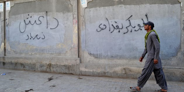 A man walks past a wall graffiti reading 'Abu Bakr al-Baghdadi', leader of the Islamic State jihadist group in Iraq.
