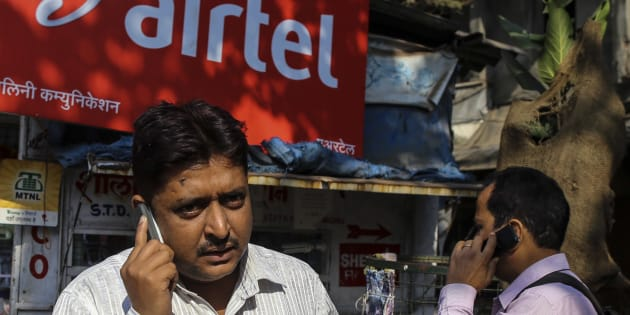 Pedestrians talk on their mobile phones in front of a store displaying a Bharti Airtel Ltd. advertisement in Mumbai, India, on Wednesday, Jan 29, 2014. The auction of wireless spectrum permits in India is scheduled for Feb. 3. Photographer: Dhiraj Singh/Bloomberg via Getty Images