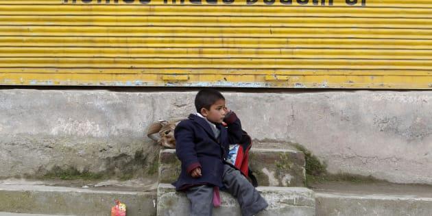 A Kashmiri school boy waits for a bus by a road side in Srinagar March 13, 2012.