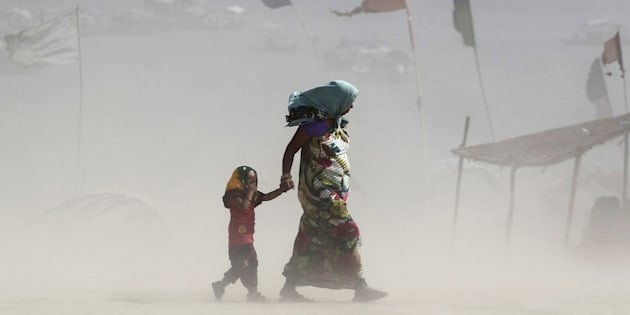 FILE PHOTO: A girl covers her eyes as she walks with her mother on the banks of the Ganges river during a dust storm on a hot summer day in Allahabad, India.