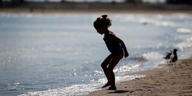 A girl is seen in silhouette by the water.