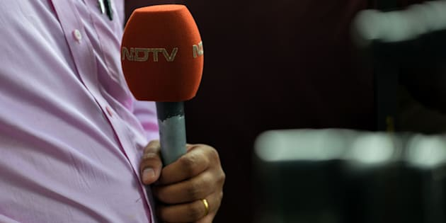 A news reporter with the Indian news channel NDTV holds a microphone in New Delhi on November 4, 2016.