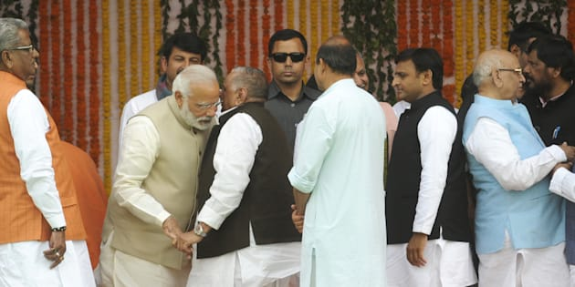 Prime Minister Narendra Modi interacting with former SP chief Mulayam Singh Yadav as well as former UP CM Akhilesh Yadav on the dais during the swearing-in ceremony at Lucknow's sprawling Smriti Upvan complex, on March 19, 2017 in Lucknow, India.