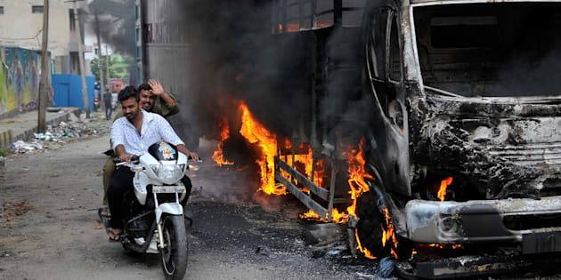 Men ride a motorcycle past a lorry in Bengaluru, which was set on fire by protesters, India September 12, 2016.