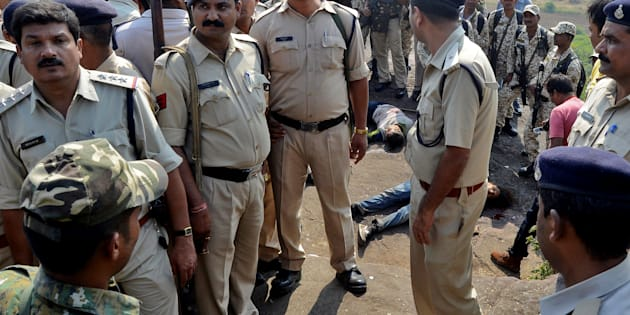 Police officers and Special Task Force soldiers stand beside dead bodies of the suspected members of the banned Students Islamic Movement of India (SIMI).