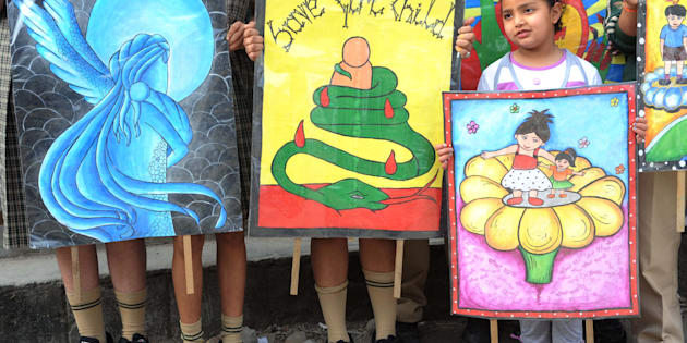 Schoolgirls pose with placards during a protest march against female foeticide.