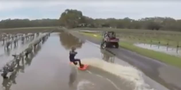 Ryland Willis being towed alongside flooded vines at Lake Breeze Wines at the flooded Fleurieu Peninsula.