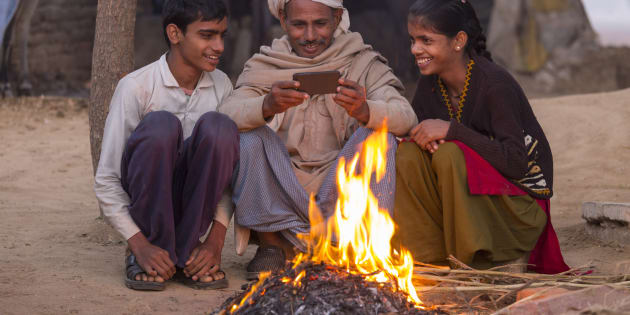 India, Uttar Pradesh, Agra, village man and his two children looking at photos on a smartphone by open fire.