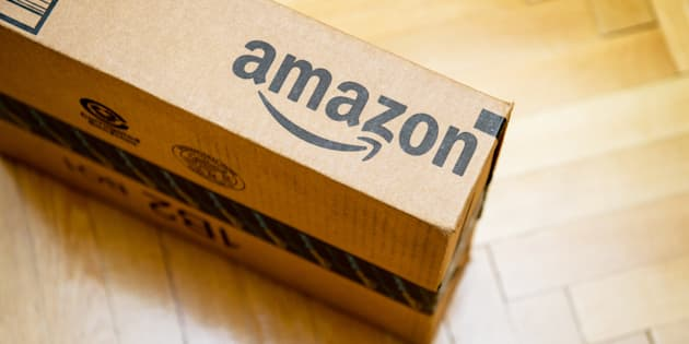 Amazon logotype printed on cardboard box side seen from above on a wooden parwuet floor.
