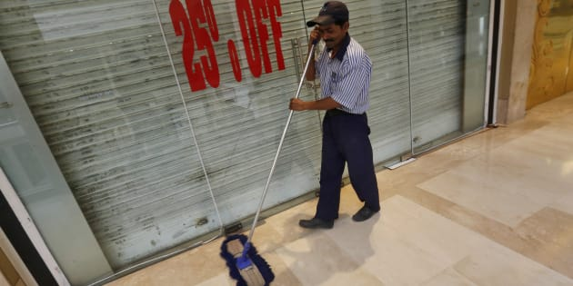 A worker mops the floor in front of a closed shop inside a MGF Metropolitan mall in New Delhi February 23, 2015.