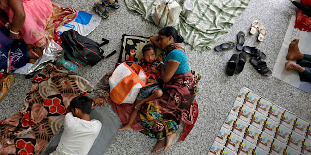 People rest on the floor outside the intensive care unit (ICU) of the Baba Raghav Das hospital in the Gorakhpur district, August 14, 2017.