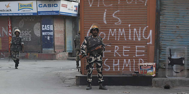 An Indian paramilitary soldier stands alert near a pro freedom graffiti in curfew.