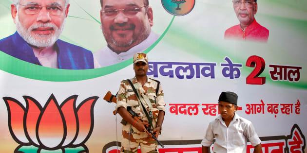 A policeman stands guard as a volunteer (bottom R) of the Hindu nationalist organisation Rashtriya Swayamsevak Sangh (RSS) looks on in front of a hoarding featuring Prime Minister Narendra Modi (L) and Amit Shah, president of India's ruling Bharatiya Janata Party (BJP). REUTERS/Jitendra Prakash