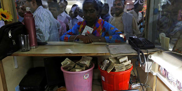 Old high denomination bank notes are seen kept in buckets at a counter as people stand in a queue to deposit their money inside a bank in the northern city of Kanpur, India, November 10, 2016. REUTERS/Adnan Abidi