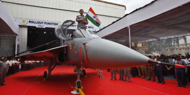 A Hindustan Aeronautics Limited engineer hurls the Indian flag as he stands in the cockpit of India's first indigenous naval Light Combat Aircraft LCA (Navy) NP1 during its roll out ceremony in Bangalore, India, Tuesday, July 6, 2010. The LCA (Navy) NP1 is capable of operation from an aircraft carrier and is now ready to undergo the phase of systems integration tests leading to ground runs, taxi trials and flight. (AP Photo/Aijaz Rahi)