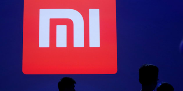 Attendants are silhouetted in front of Xiaomi's logo at a venue for the launch ceremony of Xiaomi's new smart phone Mi Max in Beijing, May 10, 2016. REUTERS/Kim Kyung-Hoon