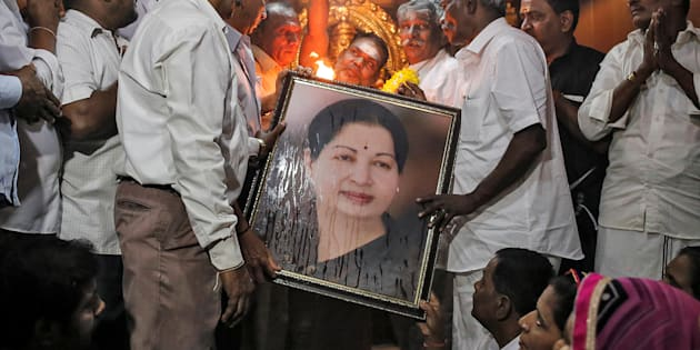 Well wishers of Tamil Nadu Chief Minister Jayalalithaa Jayaraman hold her portrait as they pray at a temple in Mumbai, India, December 5, 2016. REUTERS/Danish Siddiqui