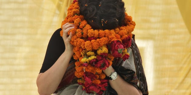 Priyanka Gandhi Vadra, daughter of India's ruling Congress party chief Sonia Gandhi, tries to remove her flower garlands as she campaigns for her mother during an election meeting at Rae Bareli in Uttar Pradesh April 22, 2014.