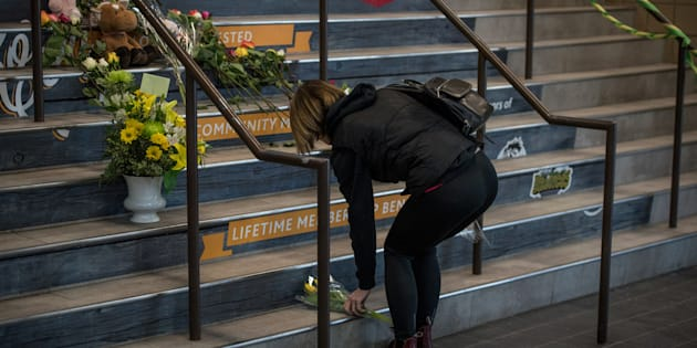 Des membres de la communauté de Humboldt déposent des fleurs sur les marches du Elgar Petersen Arena, la patinoire des Broncos.
