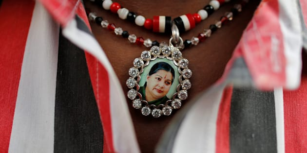 Jayalalithaa supporter wears a necklace with her picture as he attends a prayer ceremony at AIADMK office in Mumbai on 6 Dec.