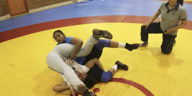 Indian wrestler Geeta Phogat (in blue) practices with a colleague as her coach Monika Choudhary (R) watches inside the Netaji Subhas National Institute of Sports in Patiala in Punjab May 5, 2012.