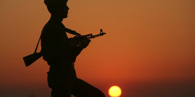 An Indian policeman is silhouetted against the setting sun as he stands guard on the banks of river Tawi ahead of India's Republic Day celebrations in Jammu January 23, 2012.