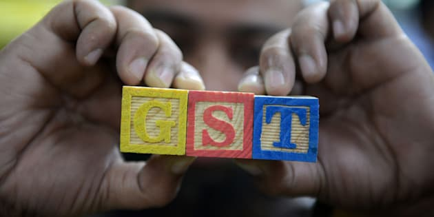 An Indian consumer goods trader shows letters GST representing 'Goods and Services Tax' (GST) at his shop in Hyderabad on August 3, 2016.