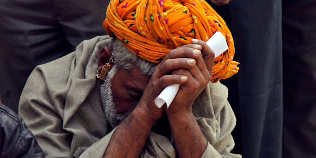 A man sits in a queue to deposit his old high denomination banknotes in Ajmer, India, November 16, 2016.