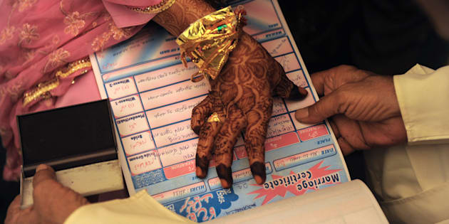 An Indian Muslim bride puts a thumb impression on a Marriage Certificate in the presence of religious leaders and a relative during the 'Nikah Kabool Hai' or 'Do You Agree for the Marriage' section of a mass wedding ceremony in Ahmedabad on October 24, 2010.