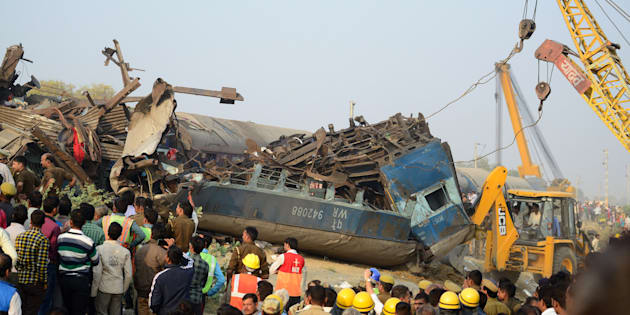 Rescue workers search for survivors in the wreckage of a train that derailed near Pukhrayan in Kanpur district on Sunday.