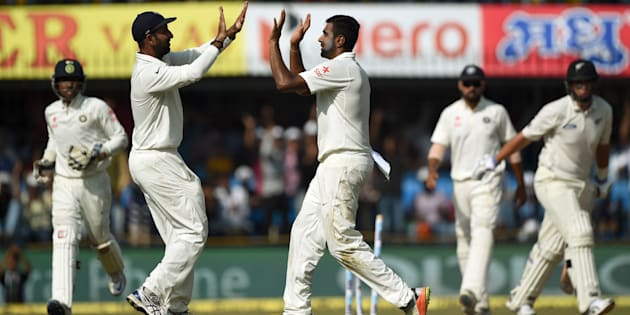 India's bowler Ravichandran Ashwin (C) celebrates with teammate Cheteshwar Pujara after taking the wicket of New Zealand batsman Ross Taylor during the fourth day of third Test cricket match between India and New Zealand at The Holkar Cricket Stadium in Indore on October 11, 2016.