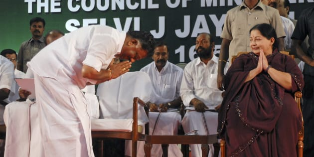 O. Paneerselvam bows to J. Jayalalithaa (R) before taking his oath as state's finance minister during a swearing-in ceremony at Madras University Centenary Auditorium in Chennai May 16, 2011.