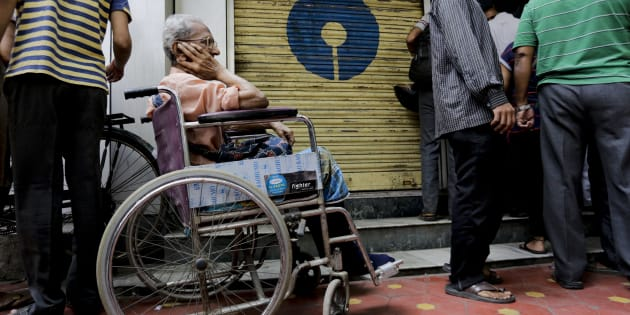 A physically disabled man on a wheel chair waits in queue to exchange or deposit discontinued currency notes outside a bank in Kolkata, India, Thursday, Nov. 10, 2016. As banks reopened after Indian Prime Minister Narendra Modi discontinued Indian currency notes in the denominations of 500 and 1000, banks in all localities were overwhelmed with large queues off people waiting to either deposit or withdraw money from their accounts. (AP Photo/Bikas Das)