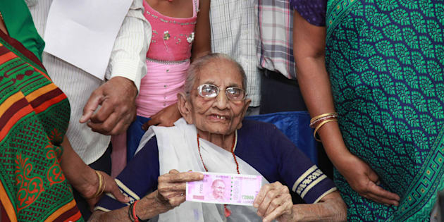 Indian Prime Minister Narendra Modi's mother (C) holds up a 2,000 rupee note after exchanging money at a bank in Rysan village, near Gandhinagar, some 30 kms from Ahmedabad on November 15, 2016.